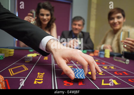People sitting at the table placing bets - Stock Photo