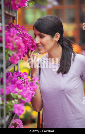 Woman smelling flowers in garden center - Stock Photo