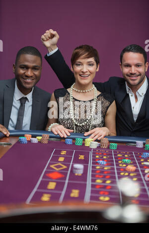 Three happy people at roulette table - Stock Photo
