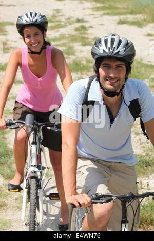 Couple enjoying leisurely bike ride - Stock Photo