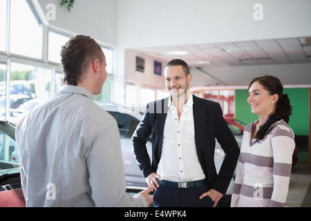 Car dealer chatting with a couple - Stock Photo