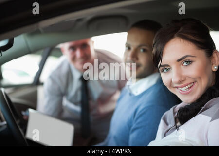 Smiling couple in a new car - Stock Photo