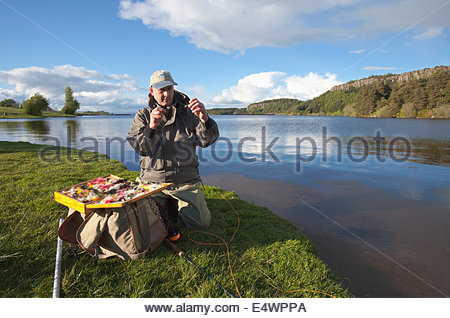 An angler chooses his fishing fly, Scotland - Stock Photo