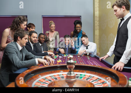 People placing bets on roulette table - Stock Photo