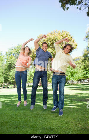 Three students jumping while raising an arm - Stock Photo