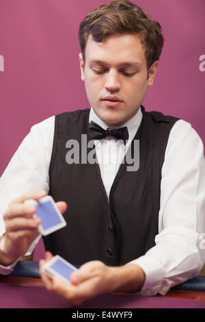 Dealer in a casino shuffling cards - Stock Photo