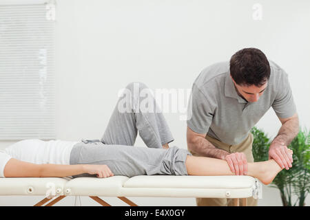 Chiropractor examining the foot of a woman - Stock Photo