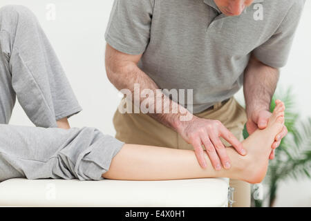 Doctor examining the foot of a woman - Stock Photo