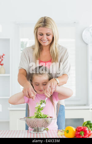 Woman and child mixing salad together - Stock Photo