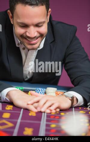 Man happily grabbing chips - Stock Photo
