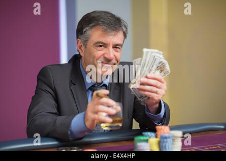 Man holding money smiling at roulette table - Stock Photo