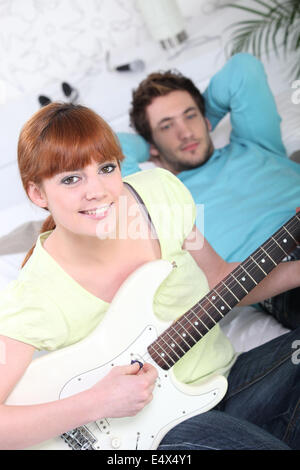 Young couple playing a guitar - Stock Photo