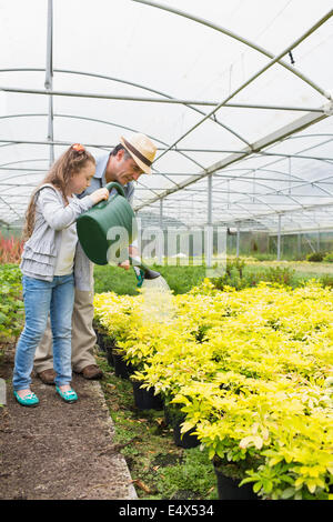 Little girl watering plants with grandfather - Stock Photo
