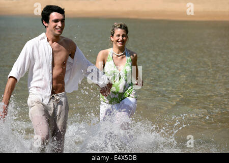 Playful young couple running through water - Stock Photo
