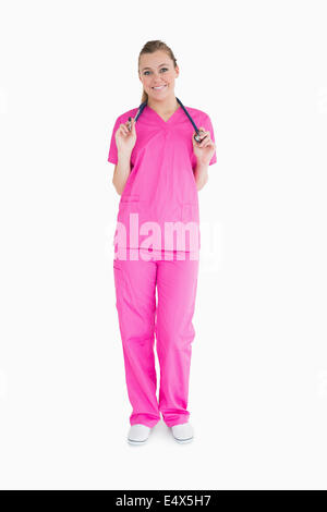 Smiling woman in pink scrubs - Stock Photo