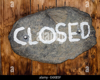 The sign 'closed', written on an oval stone, nailed to a wooden door - Stock Photo