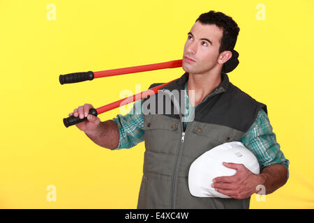 Dreamy man carrying large pliers - Stock Photo