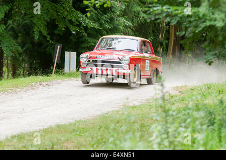bright red MK 1 ford lotus cortina competing in the forest rally stage at goodwood festival of speed 2014 - Stock Photo