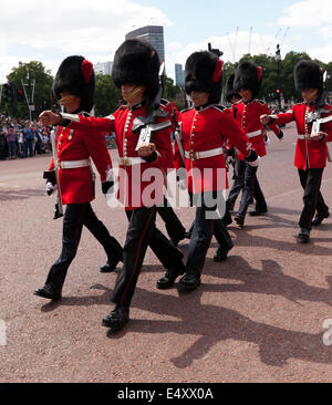 Mixed troop of Welsh Guards and Coldstream Guards  marching away from Buckingham Palace down the Mall. - Stock Photo