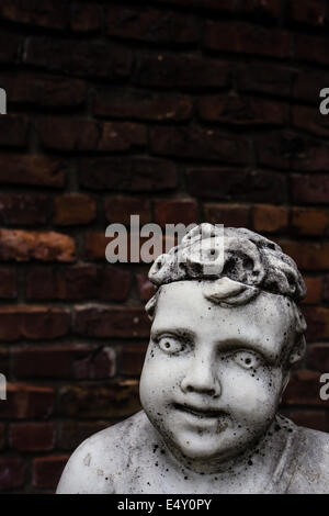 An old creepy vintage marble garden statue of a cherub or boy against and old brick wall.  Copy space above. - Stock Photo