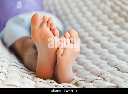 Feets in a hammock on a summer day - Stock Photo