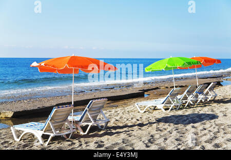 parasols and deck chairs on a sandy beach - Stock Photo