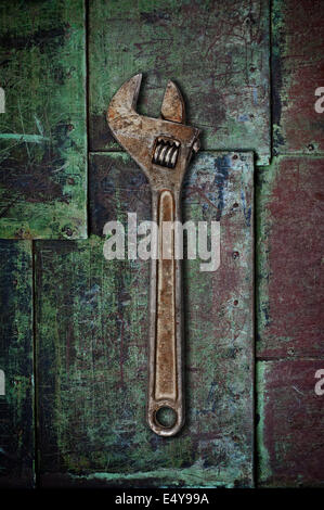 Old wrench on rusty surface. - Stock Photo