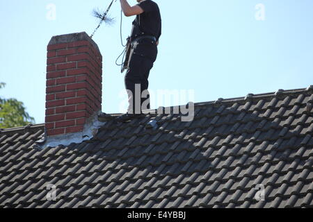 Chimney Sweep At Work On Roof Of California Coastal Home