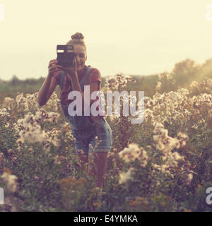 Girl photographer taking photo in the field - Stock Photo
