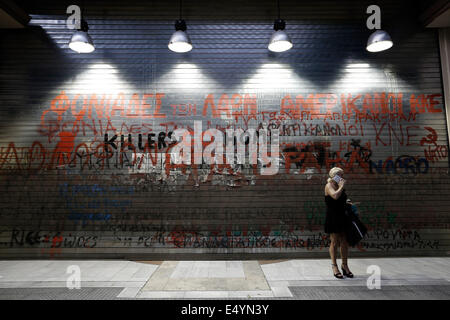 Thessaloniki, Greece. 17th July, 2014. A woman talks on the phone in front of a graffiti that reads 'Killers of - Stock Photo