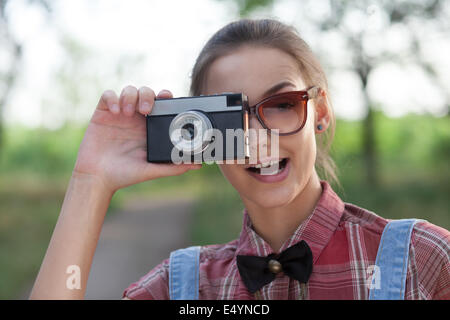 Close Up of smiling girl with retro camera - Stock Photo