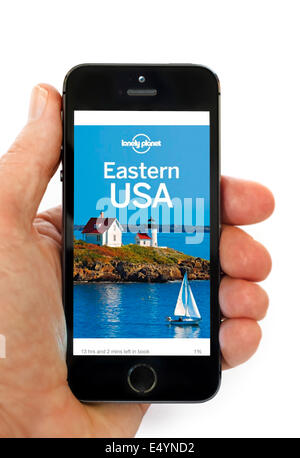 Reading a Lonely Planet trave guide on the Kindle app on an Apple iPhone 5S - Stock Photo