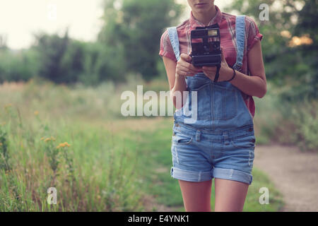 Hipster girl posing with instant camera - Stock Photo