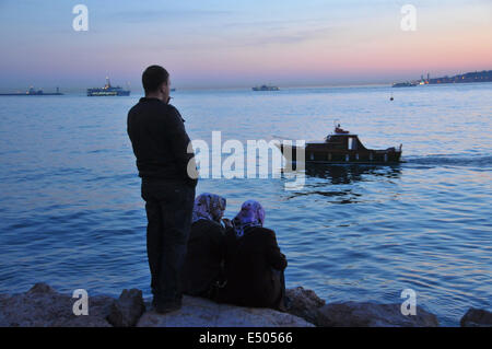 Turkish people relax on the Üsküdar waterfront at sunset. The Sea of Marmara can be seen in the far distance. - Stock Photo