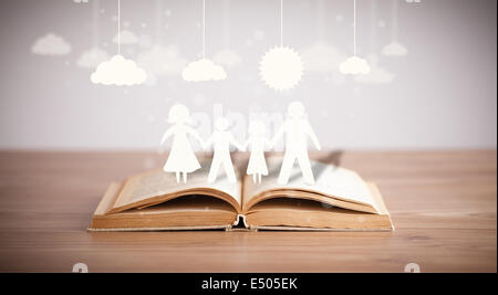 Cardboard figures of the family on opened book - Stock Photo