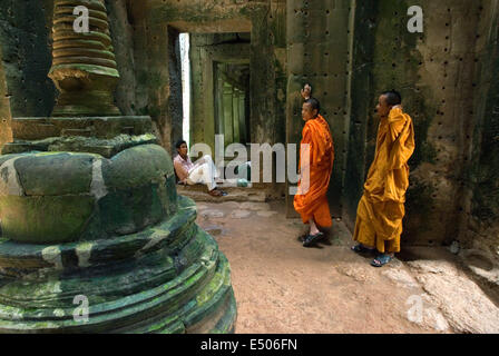 Two Buddhist monks in the inner part of the Temple Preah Khan.  Little is known about the history of Preah Khan. - Stock Photo