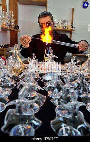 Glassblower makes glass figures of whirling dervishes, Konya, Turkey - Stock Photo