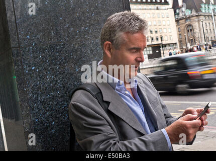 Mature businessman using an iPhone in London Southbank with blurred traditional London black cab passing in background - Stock Photo