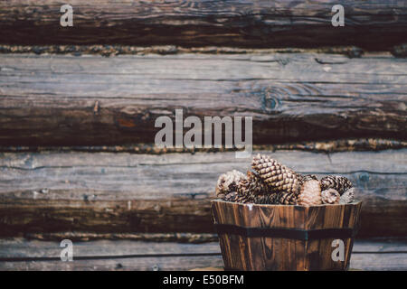 Old pine cones in wooden pot with loghouse wall at the background - Stock Photo