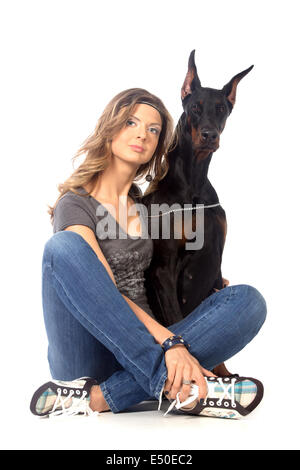 Young woman with black dobermann dog - Stock Photo