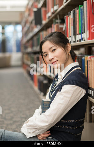 Girl sitting on the floor holding book - Stock Photo