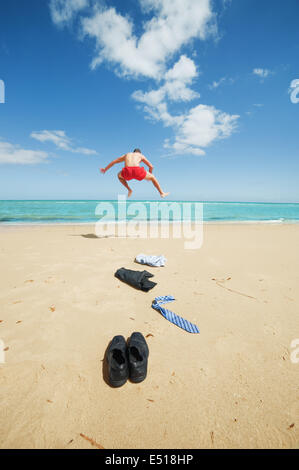 businessman jumping on the beach - Stock Photo
