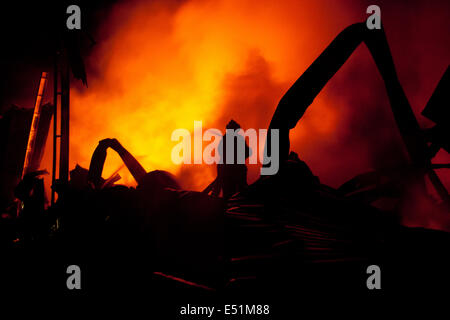 Silhouette of Firemen fighting a raging fire - Stock Photo