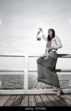 Girl on pier with kerosene lamp - Stock Photo
