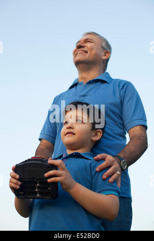 Grandfather and Boy Playing with Radio Controlled Handset, - Stock Photo
