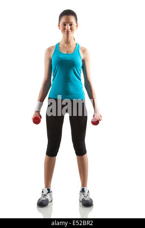 Portrait of young woman exercising with dumbbells isolated over white background - Stock Photo