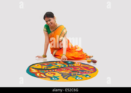 Portrait of Maharashtrian woman making a rangoli - Stock Photo