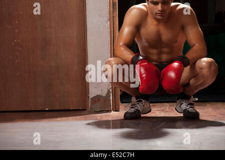 Tired male boxer crouching in gym - Stock Photo