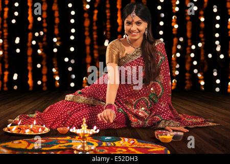 Portrait of woman making a rangoli - Stock Photo