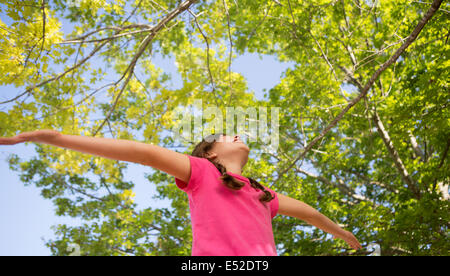 A young girl with braids wearing a pink top with her arms outstretched and head back. - Stock Photo